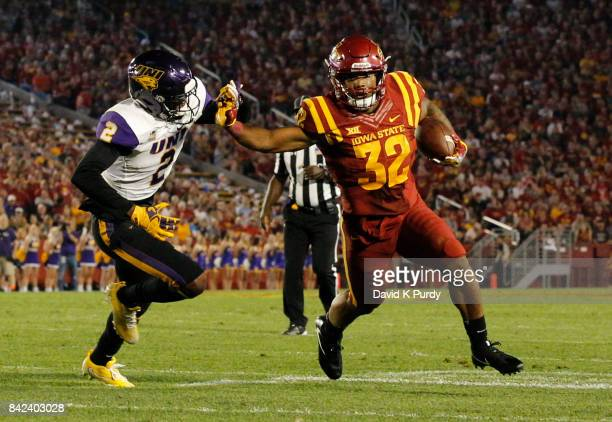 Running back David Montgomery of the Iowa State Cyclones drives the ball to the end zone as defensive back Malcolm Washington of the Northern Iowa...