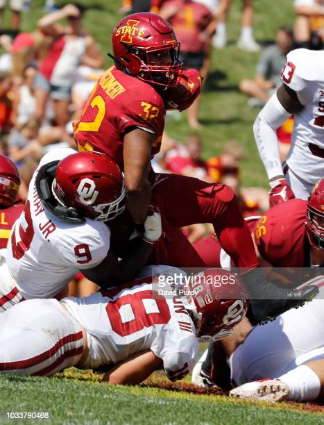 Running back David Montgomery of the Iowa State Cyclones is tackled by linebacker Kenneth Murray of the Oklahoma Sooners and linebacker Curtis Bolton...