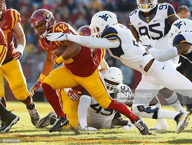 Running back David Montgomery of the Iowa State Cyclones is tackled by safety Kyzir White of the West Virginia Mountaineers as he rushed for yards in...