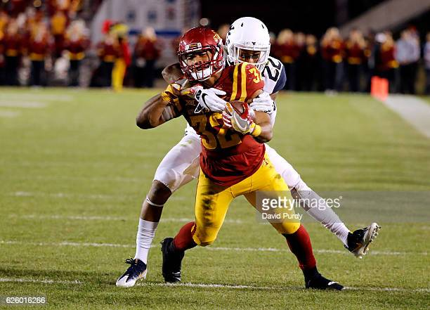 Running back David Montgomery of the Iowa State Cyclones is tackled by safety Jarrod Harper of the West Virginia Mountaineers while rushing for yards...