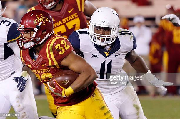 Running back David Montgomery of the Iowa State Cyclones rushes for yards as linebacker David Long of the West Virginia Mountaineers pursues in the...