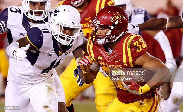 Running back David Montgomery of the Iowa State Cyclones rushes for yards as linebacker David Long of the West Virginia Mountaineers blocks in the...