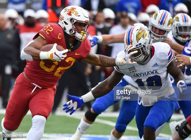 Running back David Montgomery of the Iowa State Cyclones stiff arms cornerback Julian Chandler of the Kansas Jayhawks as he rushes in the first...