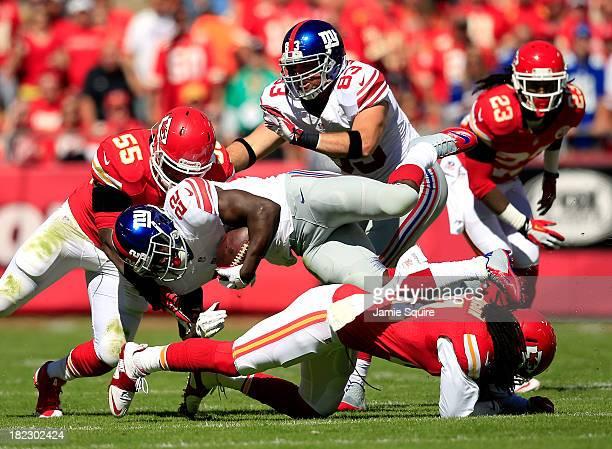 Running back David Wilson of the New York Giants is tackled by inside linebacker Akeem Jordan and cornerback Dunta Robinson of the Kansas City Chiefs...