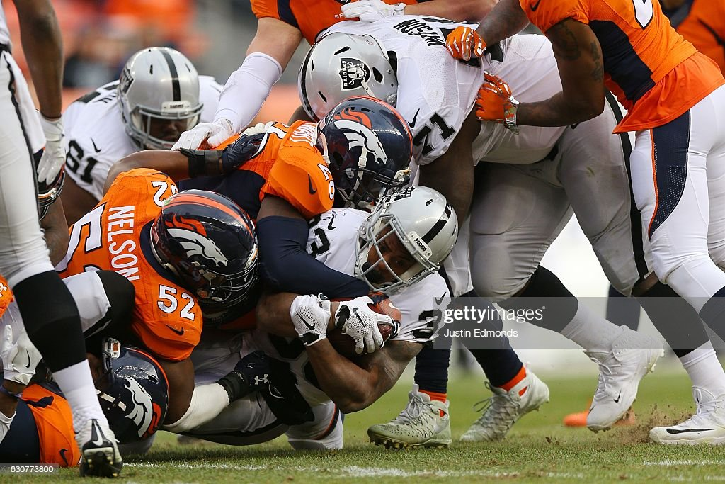 Running back DeAndre Washington #33 of the Oakland Raiders is tackled in the second quarter of the game against the Denver Broncos at Sports Authority Field at Mile High on January 1, 2017 in Denver, Colorado.