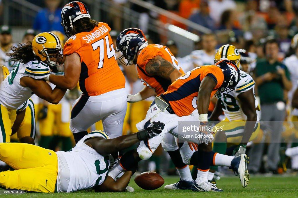 Running back De'Angelo Henderson #33 of the Denver Broncos fumbles the football in the fourth quarter during a Preseason game against the Green Bay Packers at Sports Authority Field at Mile High on August 26, 2017 in Denver, Colorado. The Broncos defeated the Packers 20-17.