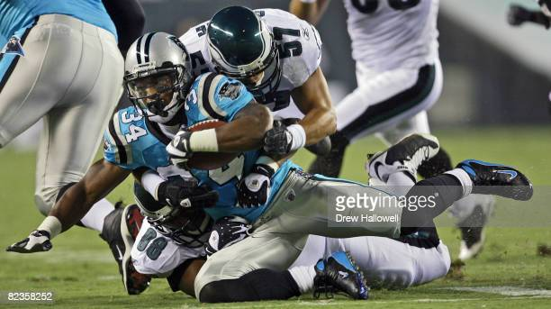 Running back DeAngelo Williams of the Carolina Panthers gets tackled by linebacker Chris Gocong and defensive tackle Mike Patterson of the...