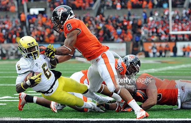 Running back De'Anthony Thomas of the Oregon Ducks is hit by safety Tyrequek Zimmerman of the Oregon State Beavers as he runs the ball in for a...