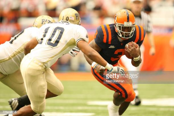 Running back Delone Carter of the Syracuse Orange runs against Mike Phillips of the University of Pittsburgh Panthers at the Carrier Dome on October...