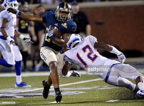 Running back Demarcus Godfrey of the Georgia Southern Eagles eludes a tackle by defensive back Isaiah Bennett of the Savannah State Tigers during the...