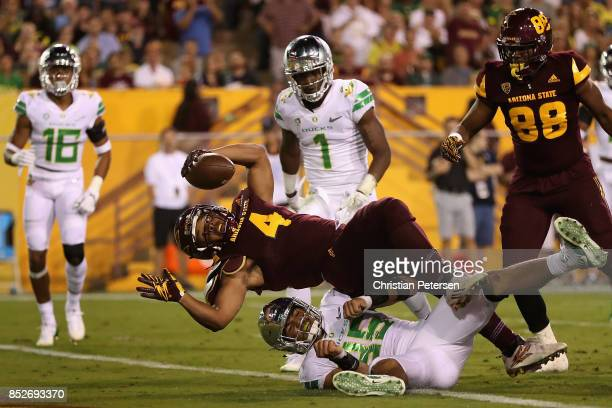 Running back Demario Richard of the Arizona State Sun Devils drives into the end zone to score a seven yard touchdown rush over linebacker Troy Dye...
