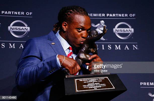 Running back Derrick Henry of the Alabama Crimson Tide kisses the Heisman Trophy during a press conference after being named the 81st Heisman...