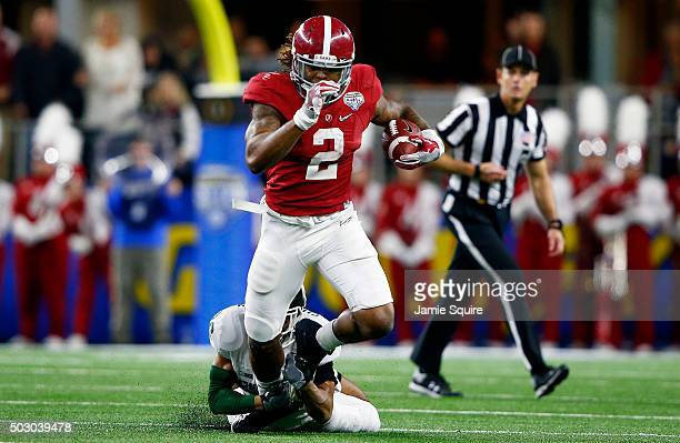 Running back Derrick Henry of the Alabama Crimson Tide runs the ball ahead of cornerback Arjen Colquhoun of the Michigan State Spartans in the second...