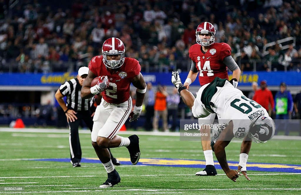 Running back Derrick Henry #2 of the Alabama Crimson Tide stiff arms defensive end Shilique Calhoun #89 and then runs for a touchdown in the fourth quarter against the Michigan State Spartans during the Goodyear Cotton Bowl at AT&T Stadium on December 31, 2015 in Arlington, Texas.