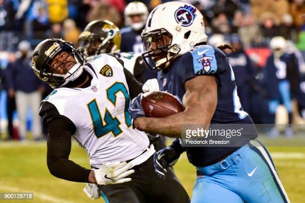 Running back Derrick Henry of the Tennessee Titans carries the ball against safety Barry Church of the Jacksonville Jaguars at Nissan Stadium on...
