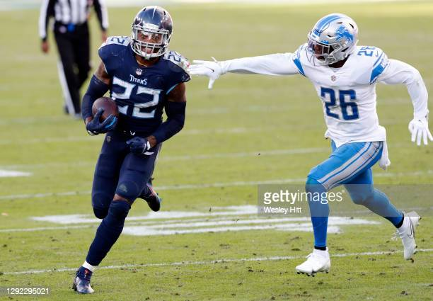 Running back Derrick Henry of the Tennessee Titans carries the football over strong safety Duron Harmon of the Detroit Lions during the game at...