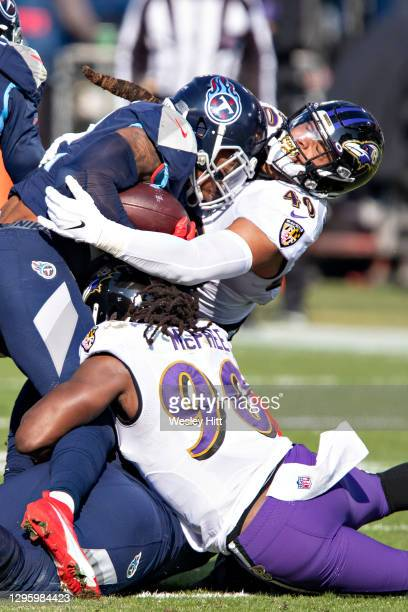 Running back Derrick Henry of the Tennessee Titans is tackled during their AFC Wild Card Playoff game by linebacker Malik Harrison and linebacker...