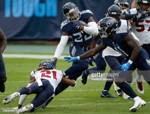 Running back Derrick Henry of the Tennessee Titans runs with the ball while being tackled by Bradley Roby of the Houston Texans in the first quarter...