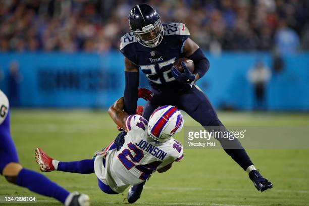 Running back Derrick Henry of the Tennessee Titans rushes in front of cornerback Taron Johnson of the Buffalo Bills during the second half at Nissan...