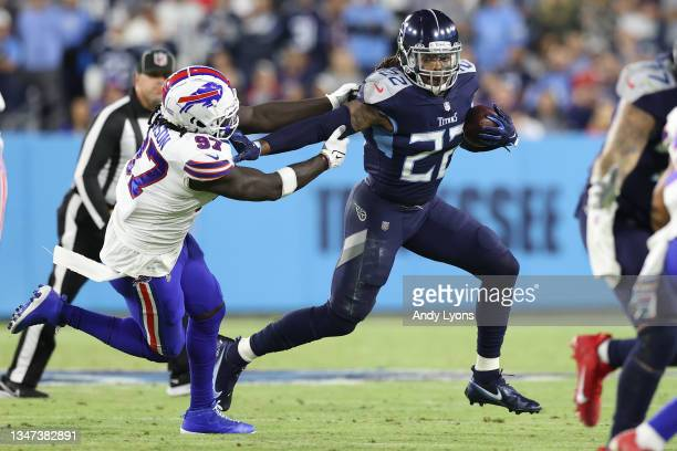 Running back Derrick Henry of the Tennessee Titans rushes past defensive end Mario Addison of the Buffalo Bills during the first half at Nissan...