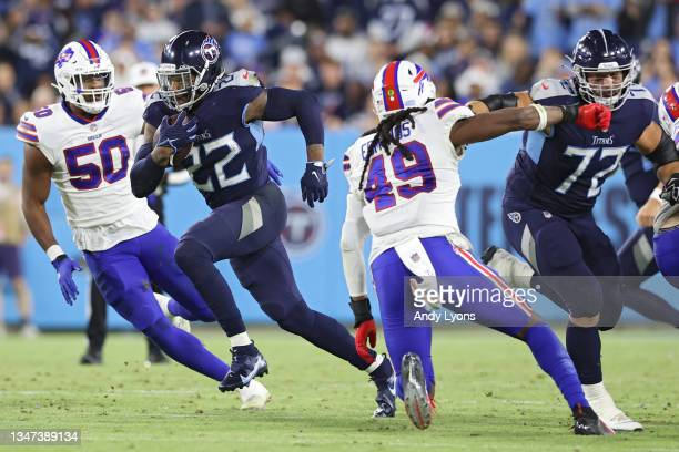 Running back Derrick Henry of the Tennessee Titans rushes past defensive end Greg Rousseau of the Buffalo Bills during the second half at Nissan...