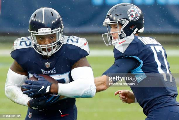 Running back Derrick Henry of the Tennessee Titans takes the hand-off from quarterback Ryan Tannehill and runs with the ball in the first quarter...