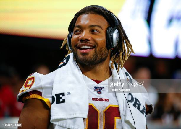 Running back Derrius Guice of the Washington Redskins has a laugh from the sidelines in the second half of an NFL preseason game against the Atlanta...