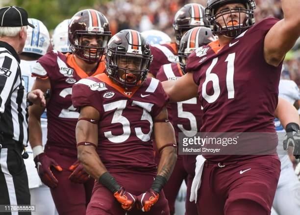 Running back Deshawn McClease of the Virginia Tech Hokies celebrates his touchdown run against the North Carolina Tar Heels with offensive lineman...