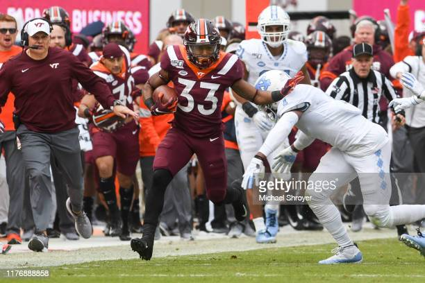 Running back Deshawn McClease of the Virginia Tech Hokies stiff arms defensive back Myles Dorn of the North Carolina Tar Heels in the first half at...