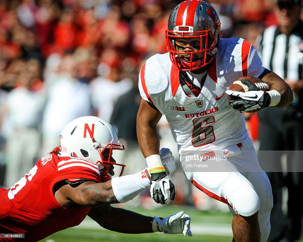 Running back Desmon Peoples #6 of the Rutgers Scarlet Knights slips past safety Corey Cooper #6 of the Nebraska Cornhuskers during their game at Memorial Stadium on October 25, 2014 in Lincoln, Nebraska. Nebraska defeated Rutgers 42-24.