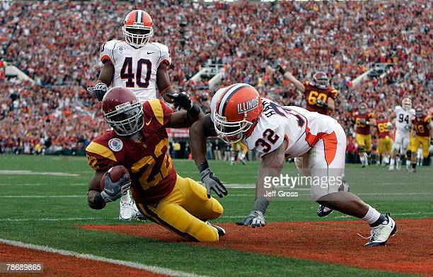 Running back Desmond Reed of the USC Trojans falls to the ground in the end zone for a touchdown after a hit by defensive back Justin Harrison of the...