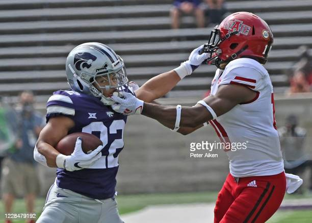 Running back Deuce Vaughn of the Kansas State Wildcats runs up field against pressure from defensive back Elery Alexander of the Arkansas State Red...