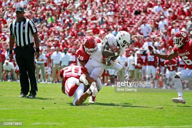 Running back Devin Singletary of the Florida Atlantic Owls is tackled by safety Robert Barnes and linebacker Caleb Kelly of the Oklahoma Sooners at...