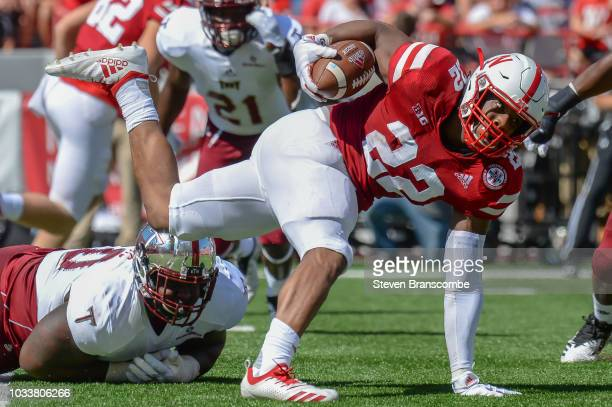 Running back Devine Ozigbo of the Nebraska Cornhuskers gets tripped up by defensive tackle Trevon Sanders of the Troy Trojans in the first half at...