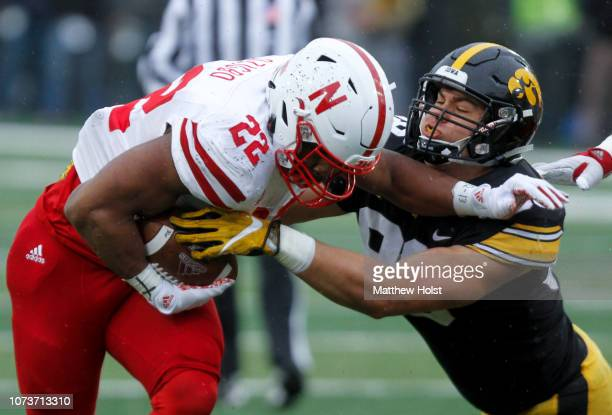 Running back Devine Ozigbo of the Nebraska Cornhuskers runs up the field in the second half against defensive end Anthony Nelson of the Iowa Hawkeyes...