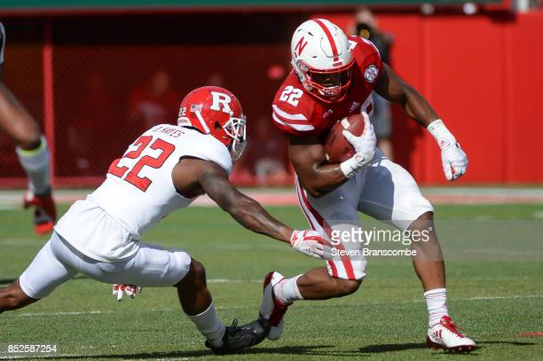 Running back Devine Ozigbo of the Nebraska Cornhuskers tries to avoide the tackle of defensive back Damon Hayes of the Rutgers Scarlet Knights at...