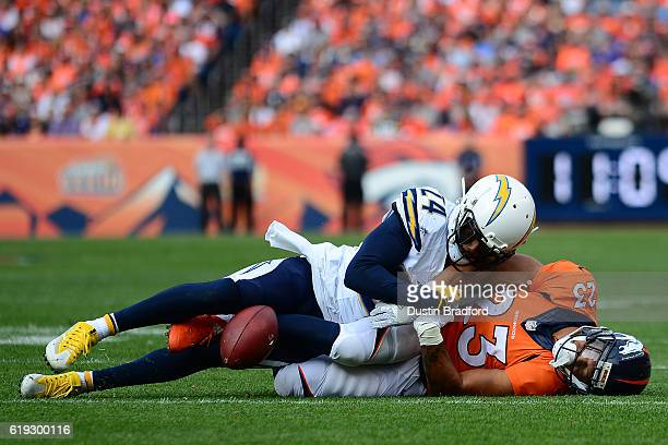 Running back Devontae Booker of the Denver Broncos is unable to catch a pass and is tackled by cornerback Brandon Flowers of the San Diego Chargers...
