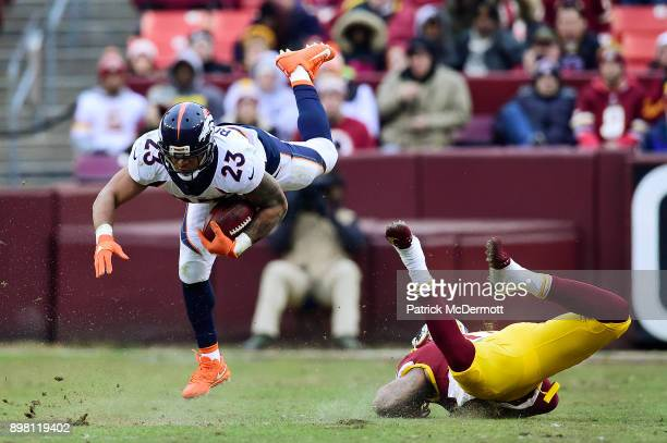 Running back Devontae Booker of the Denver Broncos is upended by linebacker Pete Robertson of the Washington Redskins in the fourth quarter at...