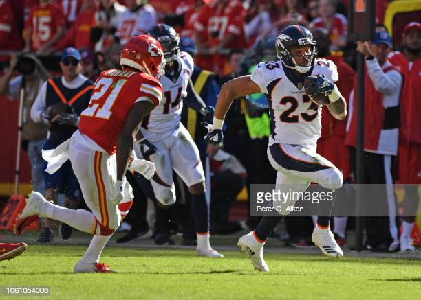 Running back Devontae Booker of the Denver Broncos runs down field during the second half against defensive back Eric Murray of the Kansas City...