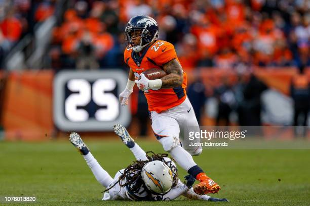 Running back Devontae Booker of the Denver Broncos rushes after avoiding a tackle attempt by strong safety Jahleel Addae of the Los Angeles Chargers...