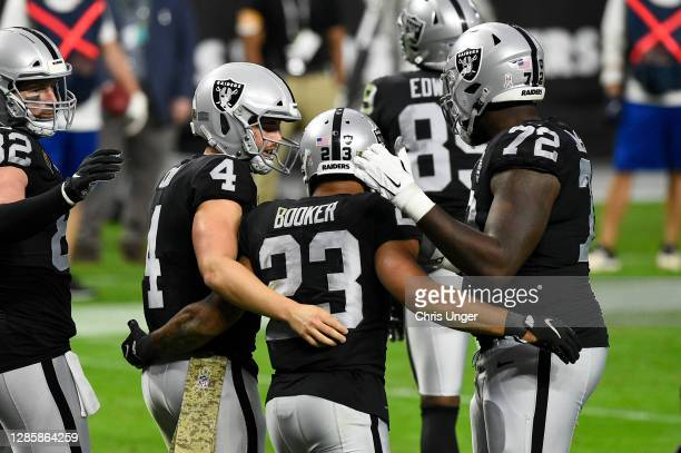 Running back Devontae Booker of the Las Vegas Raiders celebrates his touchdown against the Denver Broncos with quarterback Derek Carr and offensive...