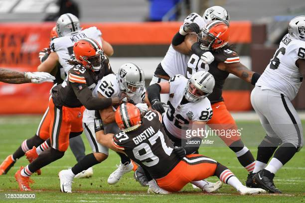 Running back Devontae Booker of the Las Vegas Raiders is tackled by Ronnie Harrison and Porter Gustin of the Cleveland Browns as he rushes the...