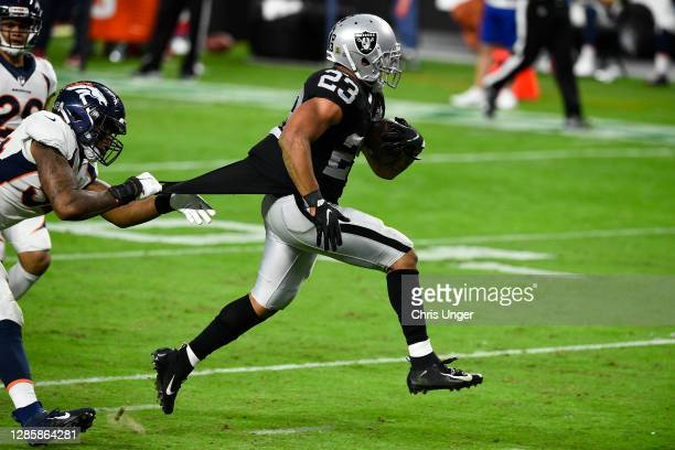 Running back Devontae Booker of the Las Vegas Raiders runs for a 23-yard touchdown against the Denver Broncos in the second half of their game at...