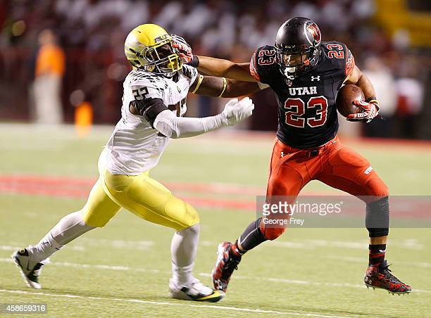 Running back Devontae Booker of the Utah Utes stiff arms linebacker Derrick Malone of the Oregon Ducks during the first half of an NCAA football game...