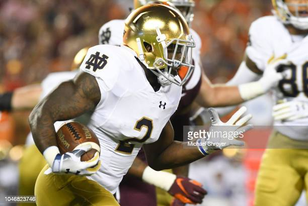 Running back Dexter Williams of the Notre Dame Fighting Irish rushes against the Virginia Tech Hokies in the first half at Lane Stadium on October 6...