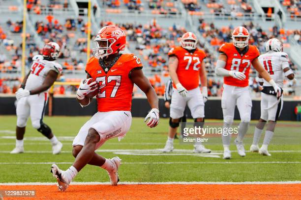 Running back Dezmon Jackson of the Oklahoma State Cowboys steps into the endzone for a touchdown after following outside the center against the Texas...