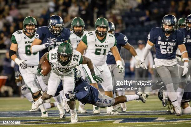 Running back Diocemy Saint Juste of the Hawaii Rainbow Warriors is tackled by defensive back Dameon Baber of the Nevada Wolf Pack at Mackay Stadium...