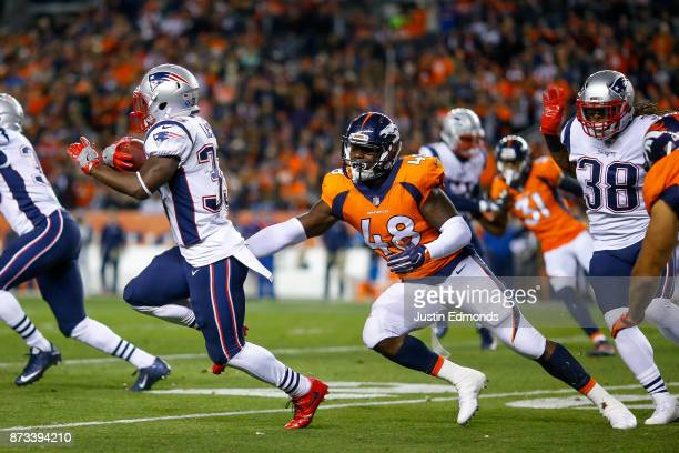 Running back Dion Lewis of the New England Patriots avoids a tackle attempt by outside linebacker Shaquil Barrett of the Denver Broncos returns a...