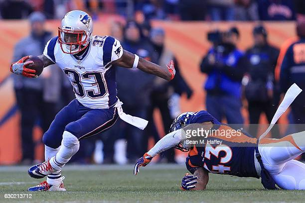 Running back Dion Lewis of the New England Patriots breaks away from a tackle attempt by strong safety TJ Ward of the Denver Broncos in the second...