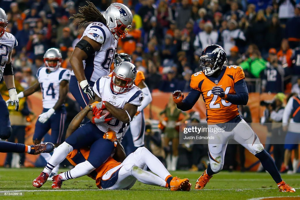 Running back Dion Lewis #33 of the New England Patriots works for a third quarter rushing touchdown against the Denver Broncos at Sports Authority Field at Mile High on November 12, 2017 in Denver, Colorado.